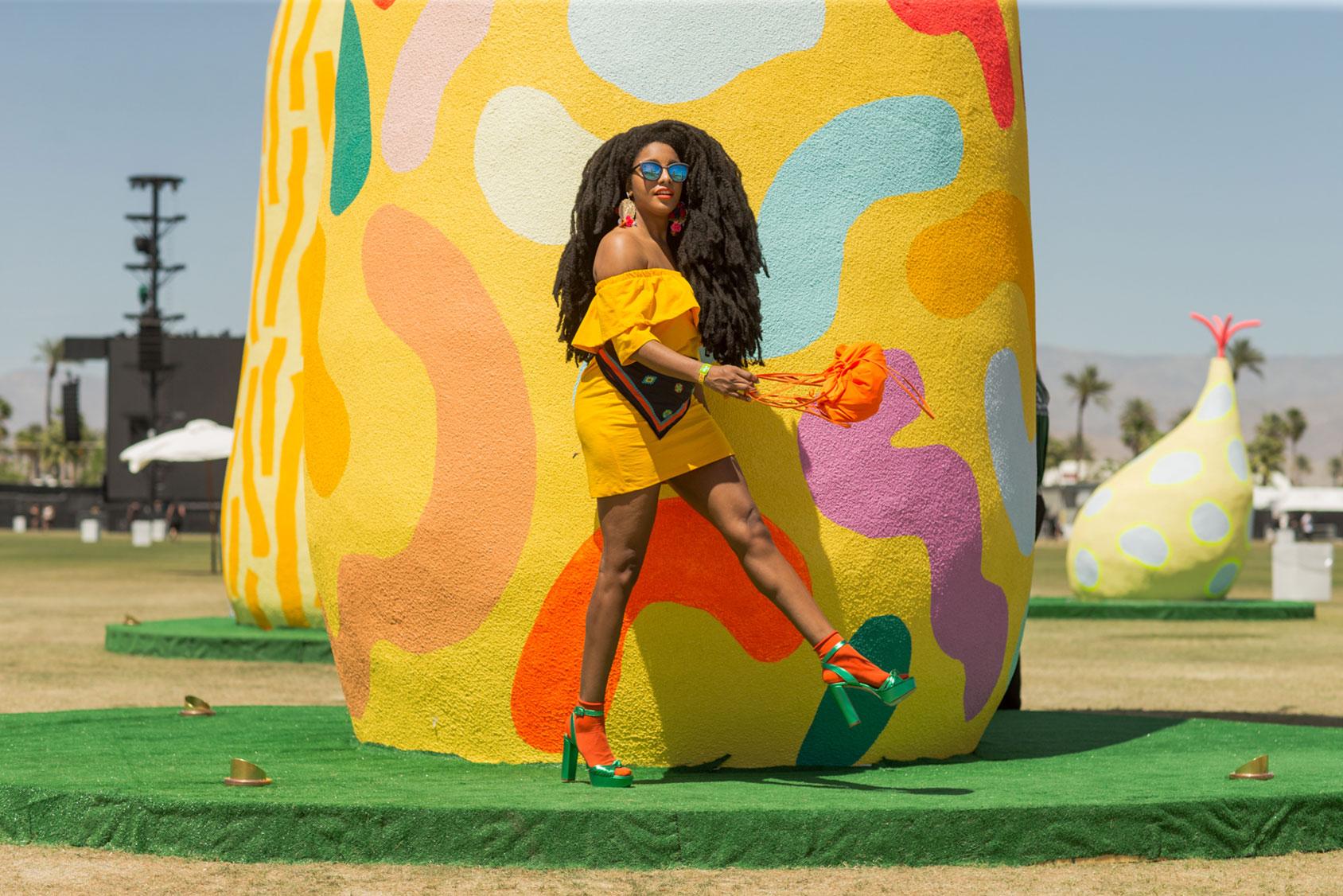 TK身着H&M春夏季系列的黄色露肩裙、搭配厚底凉鞋与橘色袜子。 她戴的围巾来自于去年的KENZO x H&M合作系列,迷你背包则属于SS16 Studio系列。